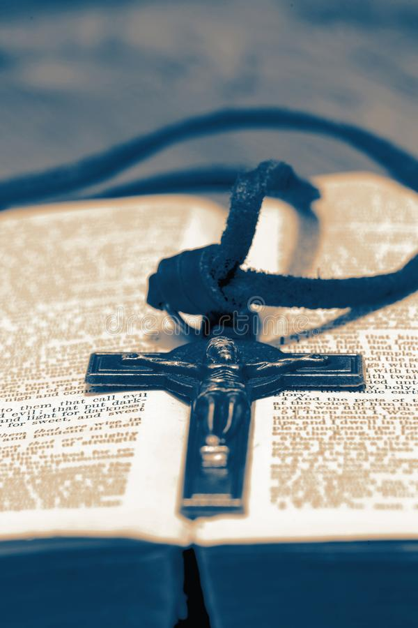 Crucifix necklace on a bible page on wood background. With toning stock images