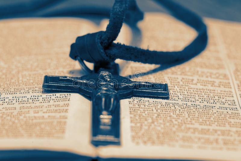 Crucifix necklace on a bible page on wood background. With toning stock photos