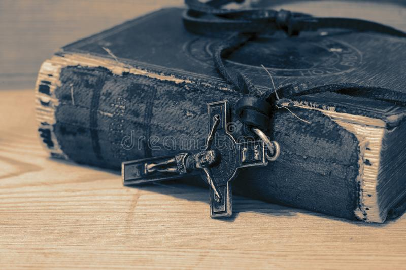 Crucifix necklace on a bible with wood background. With colour toning royalty free stock photos