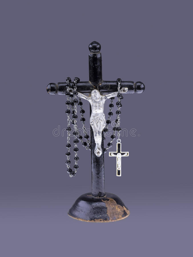 Crucifix with rosary. Close view of crucifix with rosary in a grey background stock photography