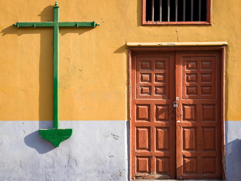Crucifix in Santa Cruz, Tenerife, Spain. Crucifix on the wall of a house with an old wooden door in Santa Cruz, Tenerife, Canary Islands, Spain stock image