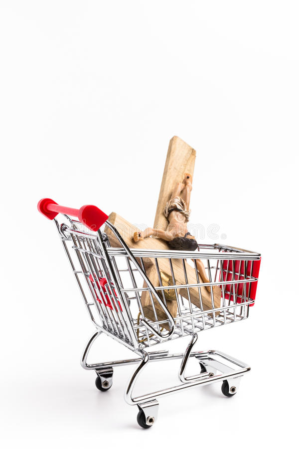 Crucifix in shopping cart. Conceptual representation of commodification of religion, loss of faith, blasphemy stock photo
