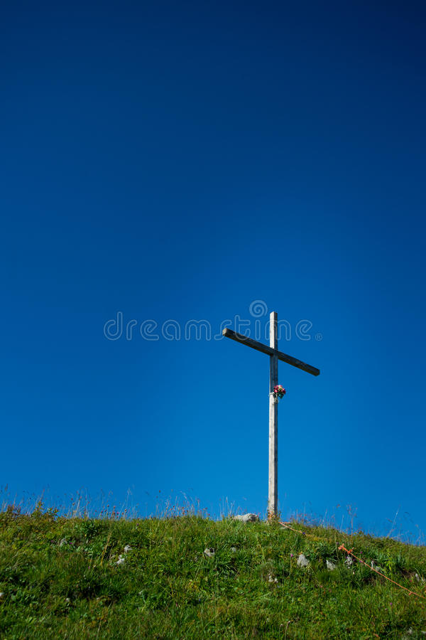 Crucifix on the top of the mountain in the middle of a meadow. Day royalty free stock images