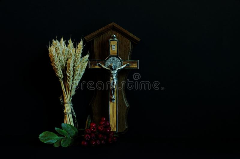 Ripe wheat ears, branch of red mountain ash and crucifix with wood inlay souvenir on black background. Symbolic concept is royalty free stock photography