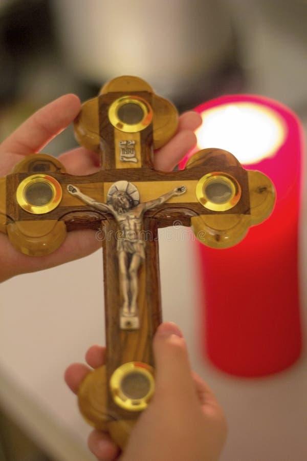 crucifixión de Jesus Christ en manos del ` s de los niños contra una vela ardiente fotos de archivo libres de regalías