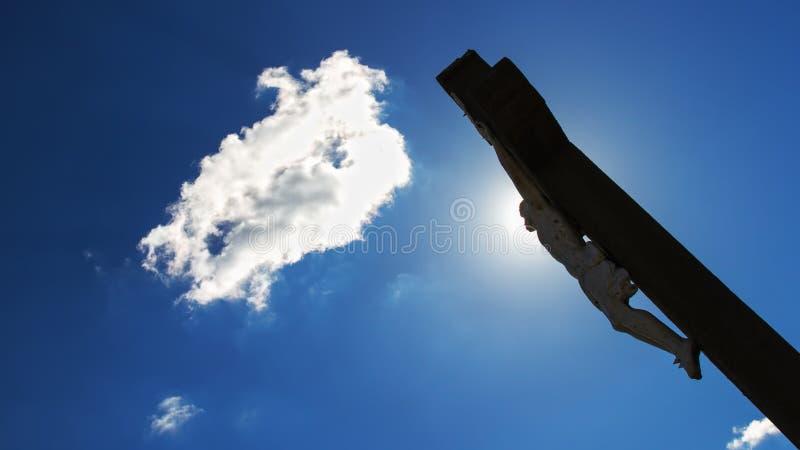 crucifixion Kristenkors med den Jesus Christ statyn över stormiga moln arkivfoton