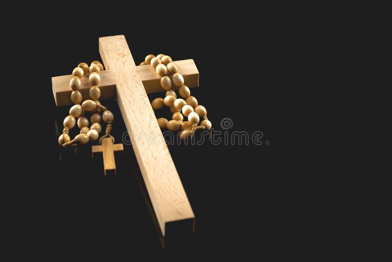 Crucifixo iluminado de madeira com um rosário em um fundo preto fotos de stock