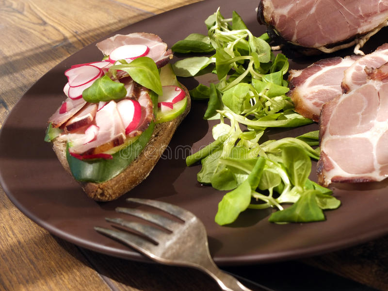 Crude, dried gammon ham with sandwich, salad on plate. On wooden board royalty free stock image