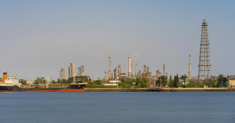 Crude oil refinery plant and many chimney with petrochemical tanker or cargo ship at coast of river on sky afternoon  bright day royalty free stock image