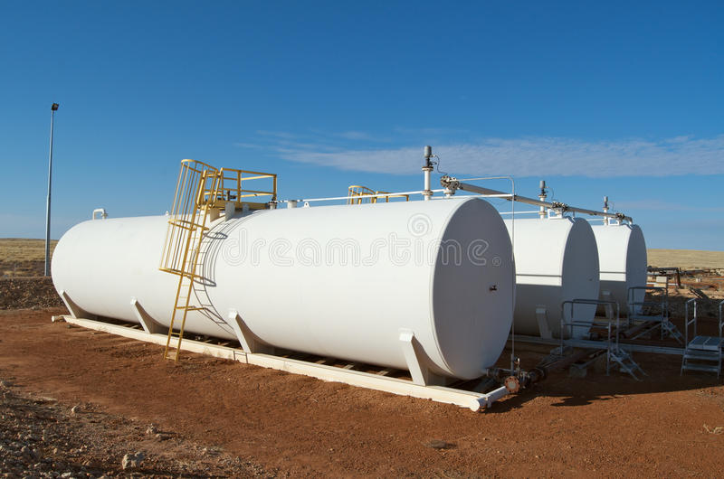 Crude oil tanks. White storage tanks of crude oil on field, outback Australia, Cooper Basin, South Australia royalty free stock image