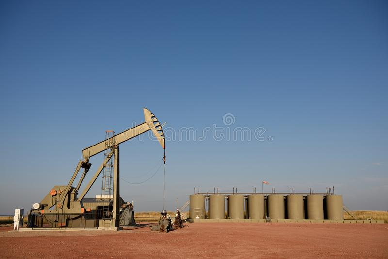 Crude oil well site pump jack and production storage tanks in the Niobrara shale. Of Wyoming, USA with copy space royalty free stock photos