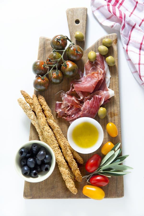 Crudo de Prosciutto carne y tomates multicolores, verde y blac imagen de archivo libre de regalías