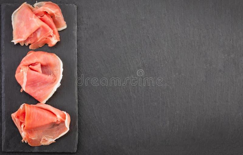 Crudo italiano do prosciutto ou jamon e salsichas espanhóis Presunto cru na placa de corte de pedra, espaço da cópia, vista super fotografia de stock royalty free