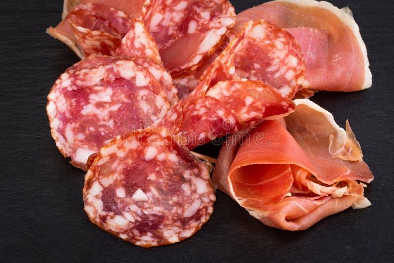Crudo italiano do prosciutto ou jamon e salsichas espanh?is Presunto cru na placa de corte de pedra fotos de stock royalty free