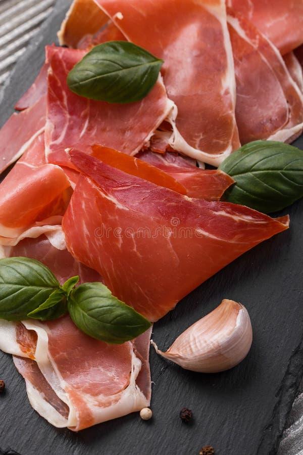Crudo italiano do prosciutto ou jamon espanhol em um fundo de madeira da placa da pedra imagens de stock royalty free