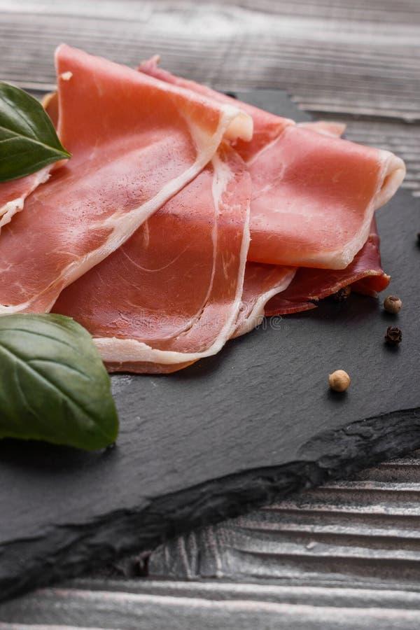 Crudo italiano do prosciutto ou jamon espanhol em um fundo de madeira da placa da pedra foto de stock