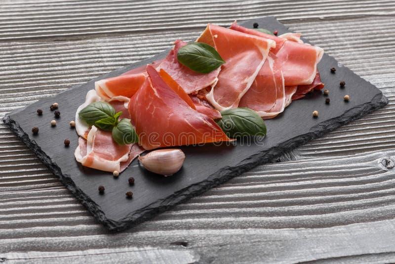 Crudo italiano do prosciutto ou jamon espanhol em um fundo de madeira da placa da pedra foto de stock royalty free
