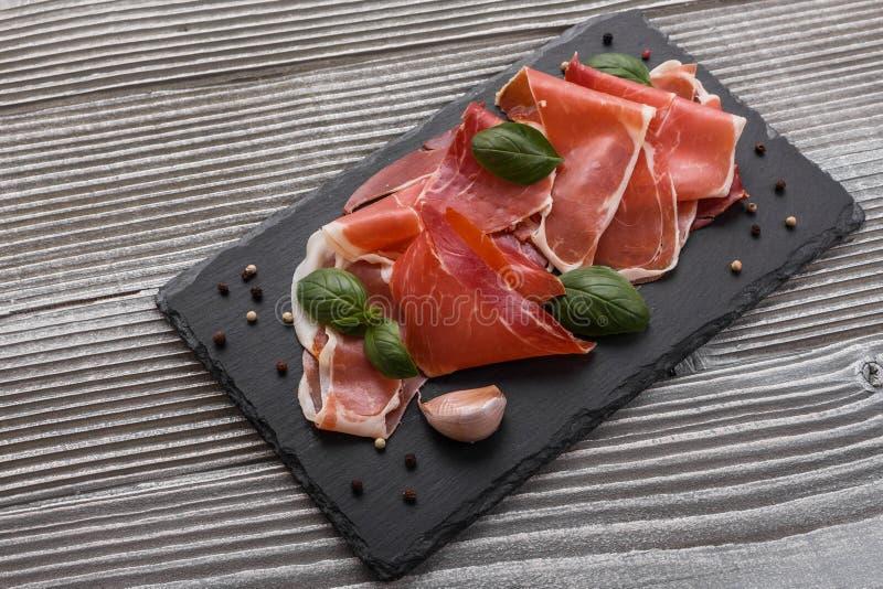 Crudo italiano do prosciutto ou jamon espanhol em um fundo de madeira da placa da pedra fotografia de stock royalty free