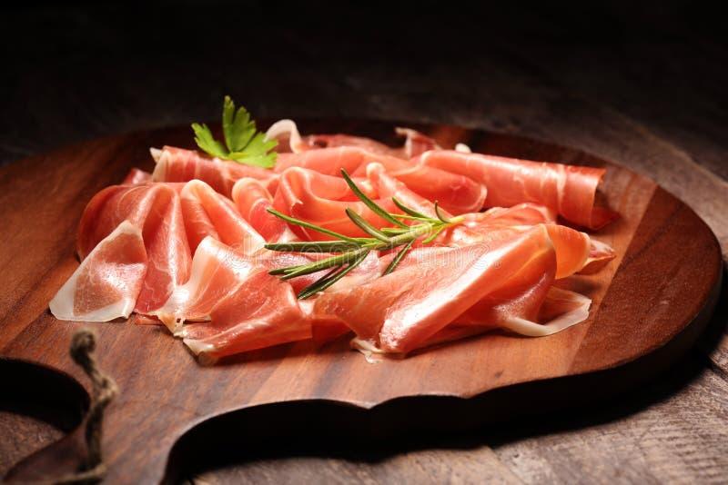 Crudo ou jamon italiano do prosciutto com alecrins Presunto cru na placa de madeira foto de stock royalty free