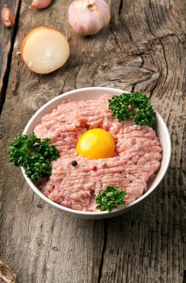 Crudo triti la carne di maiale con il tuorlo d'uovo e le erbe fotografia stock