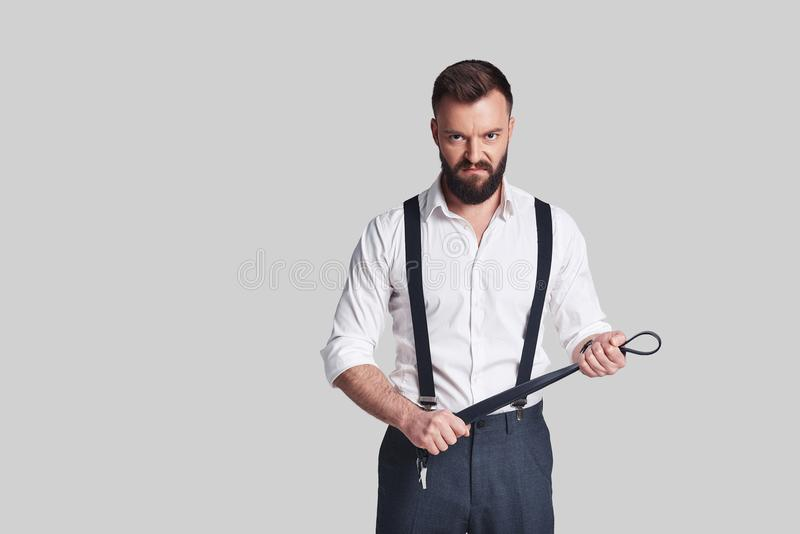 So cruel! Angry young man in formalwear carrying a belt and look. Ing at camera while standing against grey background stock photos