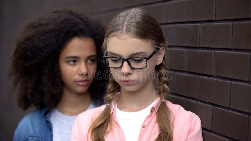 Cruel black student bullying caucasian schoolgirl eyeglasses, emotional pressure. Stock photo stock image