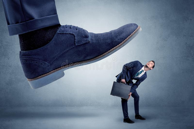Cruel boss tramping his employee. Big foot trying to crush small man who is afraid of that royalty free stock photography