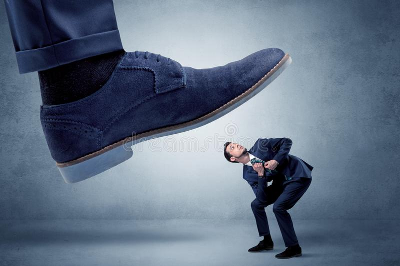 Cruel boss tramping his employee. Big foot trying to crush small man who is afraid of that stock photos