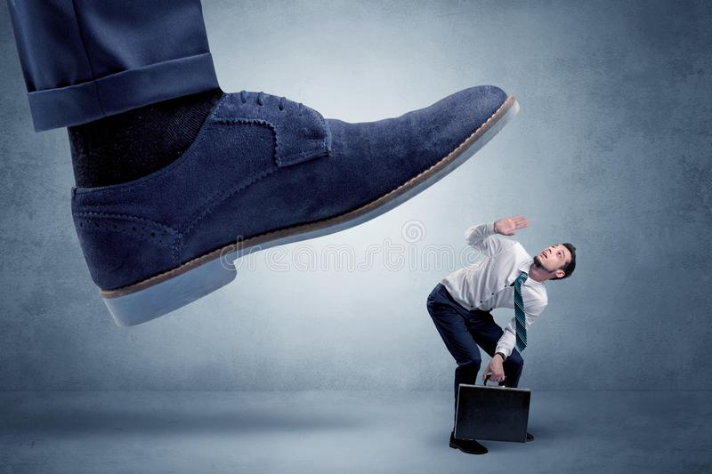 Cruel boss tramping his employee. Big foot trying to crush small man who is afraid of that stock photo