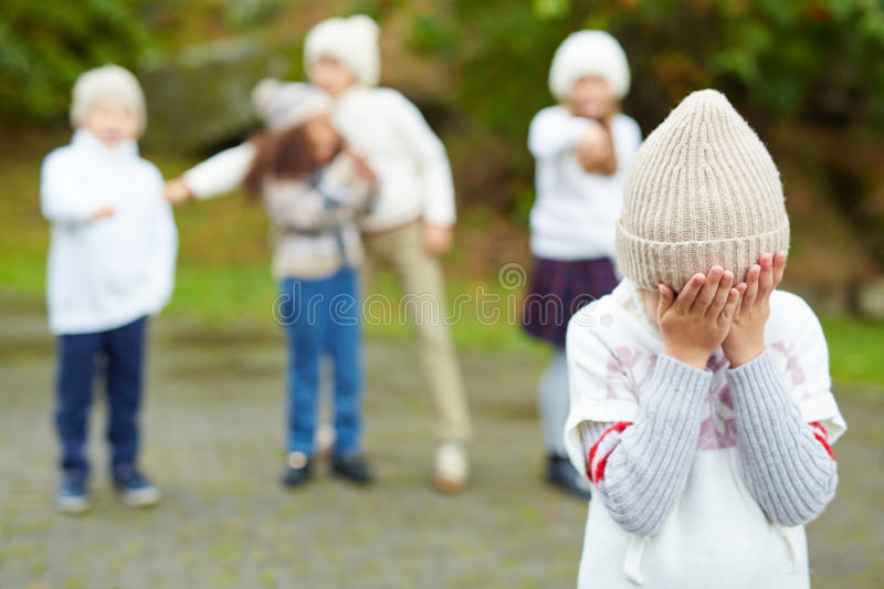 Cruel Children on Playground. Portrait of little boy crying hiding his face with cruel kids pointing at him in background, bullying and calling him names royalty free stock image