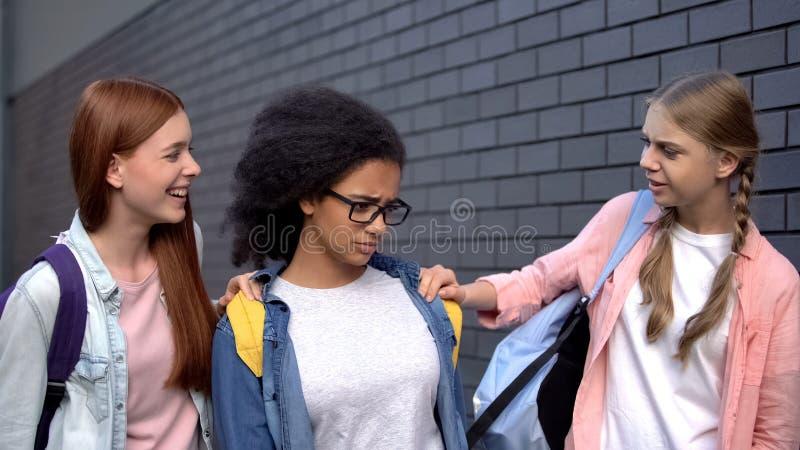 Cruel high school schoolgirls hitting black student, racism humiliation, abuse. Stock photo stock photos