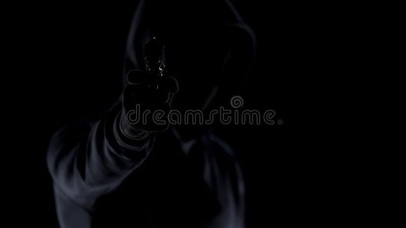Cruel killer in black clothes aiming gun at camera, contract murder, shooting. Stock photo royalty free stock photography