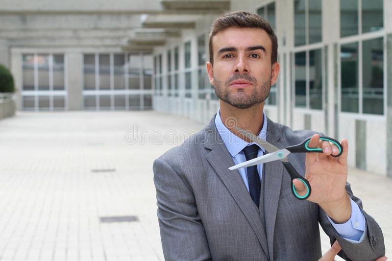 Cruel looking businessman cutting something important royalty free stock photo