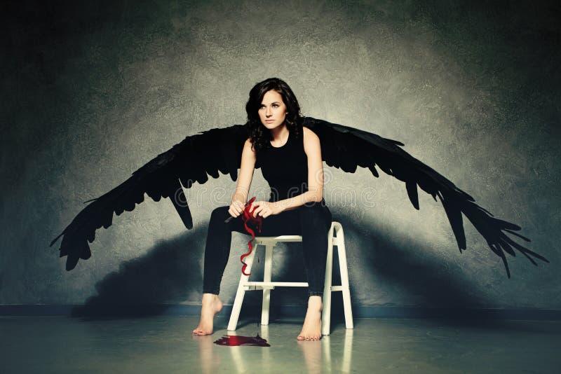 Cruel Love. Woman Black Angel Peeling a Heart. Cruel Love. Woman Black Angel Peeling a Red Heart royalty free stock images