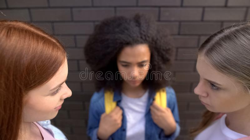 Cruel schoolgirls looking each other, scared black classmate background, abuse. Stock photo royalty free stock photography