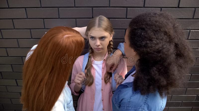 Cruel schoolgirls pushing younger teenager against wall, psychological pressure. Stock photo royalty free stock images