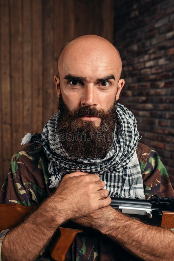 Cruel terrorist in uniform with kalashnikov rifle. Male mujahadeen with weapon. Terrorism and terror, soldier in khaki camouflage royalty free stock photos