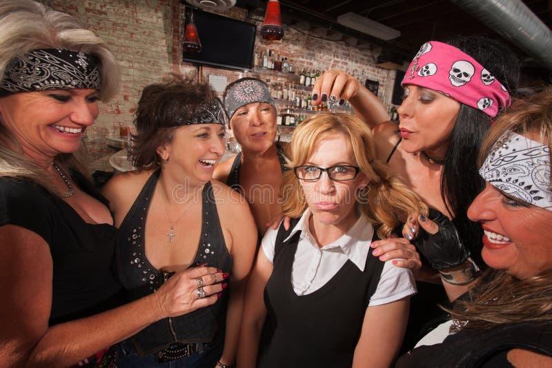 Cruel Women Teasing Nerd. Cruel gang of mature women teasing a nerd in a bar royalty free stock photography