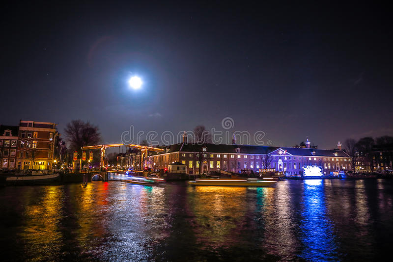 Cruise boats rush in night canals. Light installations on night canals of Amsterdam within Light Festival at full moon. royalty free stock photos