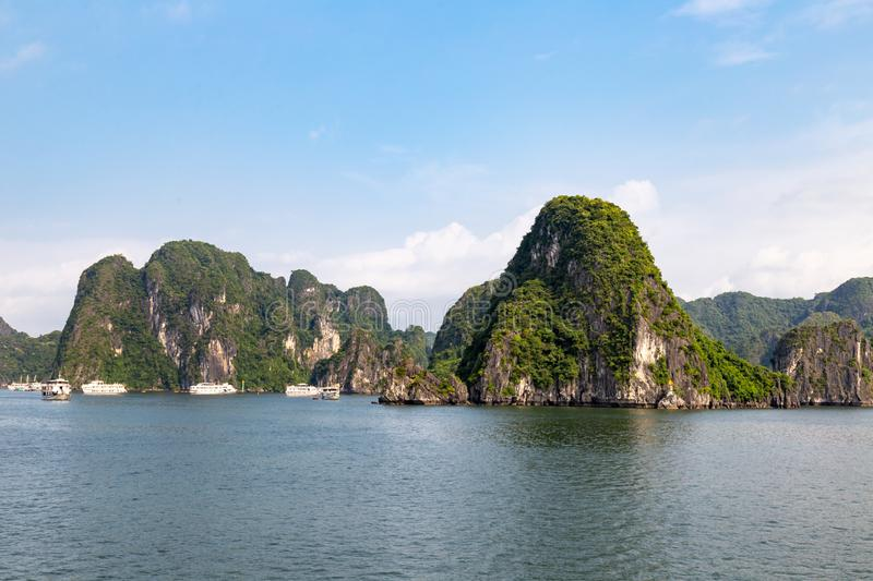 Cruise boats sailing among the karst formations in Halong Bay, Vietnam, in the gulf of Tonkin stock image