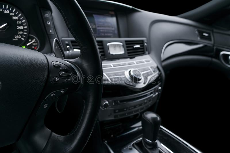 Cruise control buttons on the steering wheel of a modern car with black perforated leather interior. Modern car interior details.  royalty free stock photos