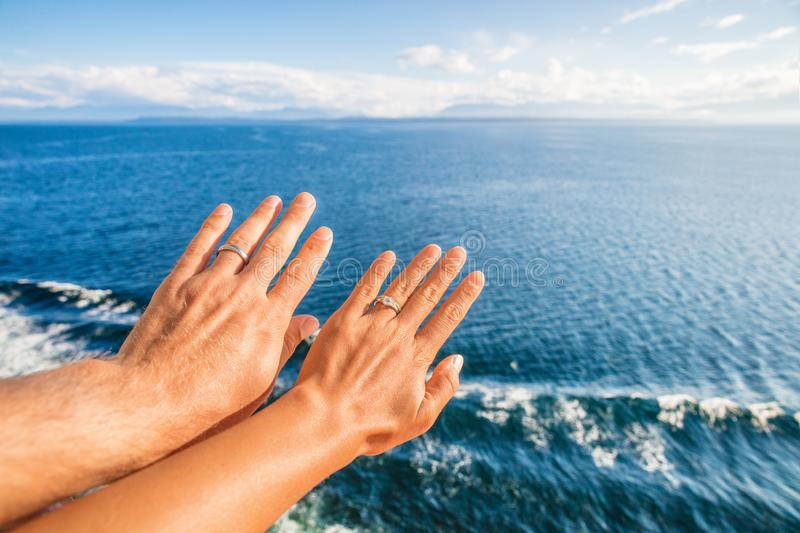 Cruise honeymoon travel vacation for newlyweds couple showing wedding rings on hand selfie at ocean view resort background. Luxury stock images