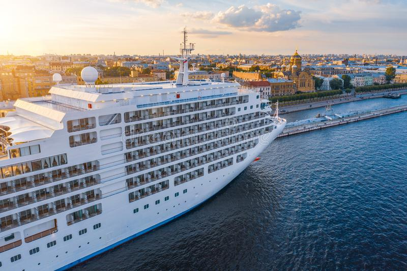 Cruise liner moored at the embankment in the waters of the river in the evening at sunset. Aerial top front side view stock image