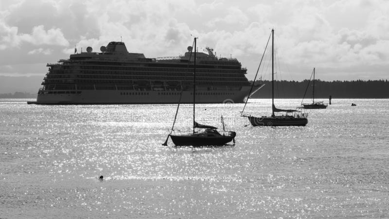 Cruise liner on the shimmering waters of a harbor. Black and white royalty free stock image