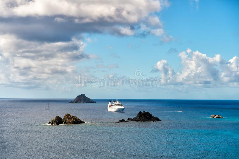 Cruise ship in blue sea on cloudy sky in gustavia, st.barts. Travel by water, discovery and adventure. Vessel and marine transport stock images