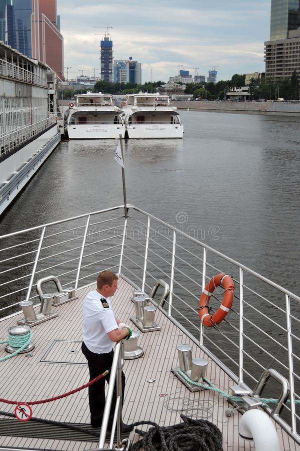 Cruise ship captain stands on a deck. Moscow city panorama. Color photo