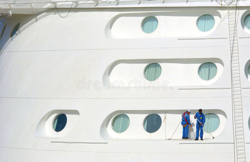 Cruise Ship Cleaning. Two workers meticulously cleaning a cruise ship using safety harness stock photography