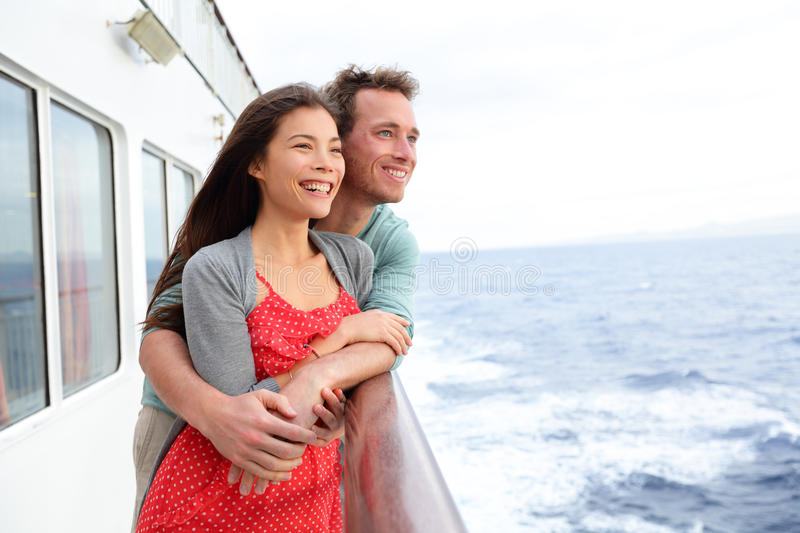 Cruise ship couple romantic enjoying travel. On boat embracing looking at view. Happy lovers traveling on vacation sailing on open sea ocean enjoying romance