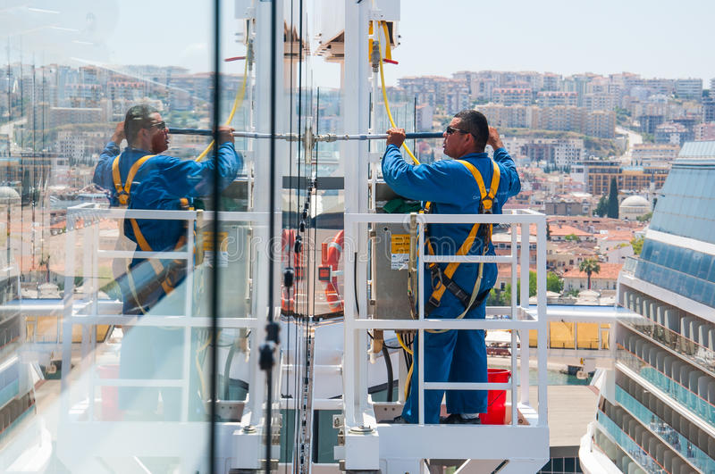 Cruise ship crew member. Working on hights using harness equipment, Celebrity Reflection, Celebrity Cruises stock photo