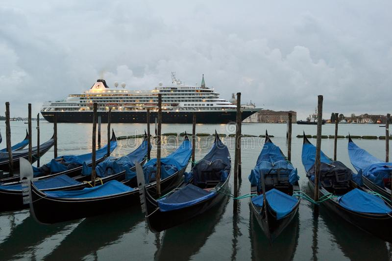 A cruise ship crossing the Venice lagoon early spring morning at dawn and blue gondolas anchored at the seafront. royalty free stock photography